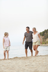 Parents with daughter walking on beach