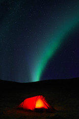 Aurora borealis over tent at night