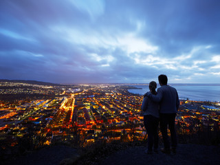 Couple looking at illuminated city at dusk