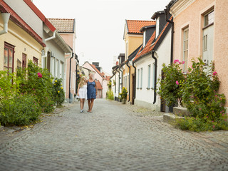 Mother with daughter walking through quiet street