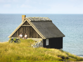 Couple sitting near wooden house at sea