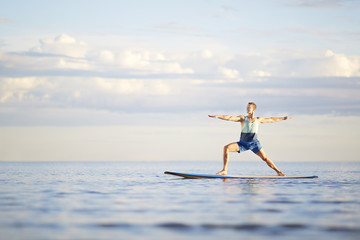 Man doing yoga on paddleboard