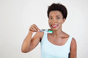 Smiling young woman brushing her teeth.
