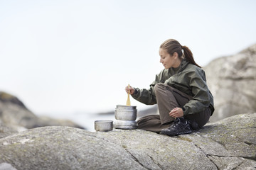 Woman preparing food on rocks