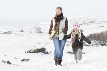Woman walking with daughter at winter