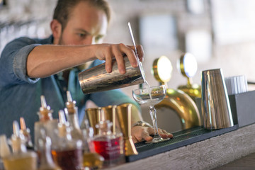 Barman preparing drink behind bar