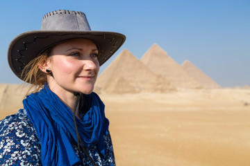 Portrait of woman with hat in front of the Great pyramid of Giza complex, Egypt.