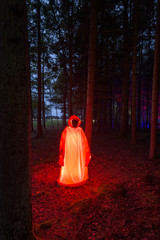 Illuminated human figure in red robe in forest