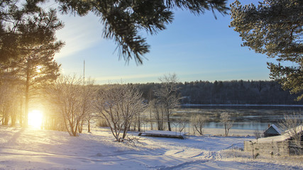 Winter landscape in Russian village during sunset. Snow, river in the background.