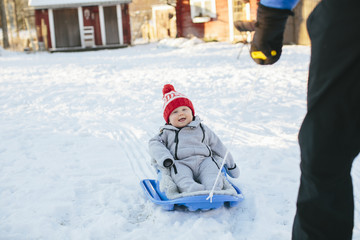 Parent pulling baby on sledge