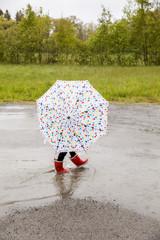 Child with umbrella walking through puddle