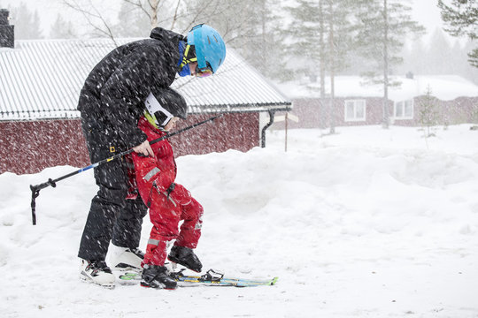 Father with child skiing together