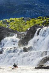 Man kayaking near waterfall