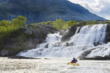 Man kayaking near waterfall