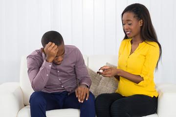 Sad Expectant Couple Sitting On Sofa
