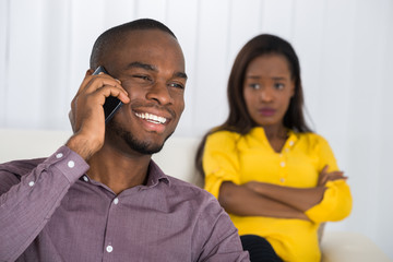 Woman Looking At Man Talking On Cellphone