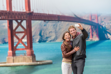 Wall Mural - Happy young couple tourists taking selfie in San Francisco by Golden Gate Bridge. Interracial young modern couple using smart phone. Asian woman, Caucasian man.