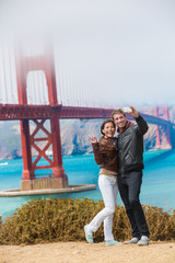 Tourists couple taking selfie photo in San Francisco by Golden Gate Bridge. Interracial young modern couple using smart phone by famous american landmark. Asian woman, Caucasian man.