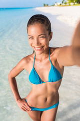 Summer vacation woman beach babe taking selfie of her beach body during travel holidays for Social Media. an. Happy mixed race Caucasian / Asian Chinese woman taking self portrait having fun.