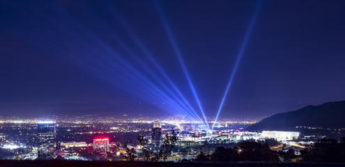 Huge spotlight rays over the night panorama of Los Angeles city