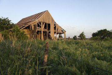 Decaying barn behind fence in field at sunset