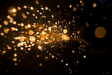 Glowing flow of steel metal spark dust particles and bokeh shine in the dark background