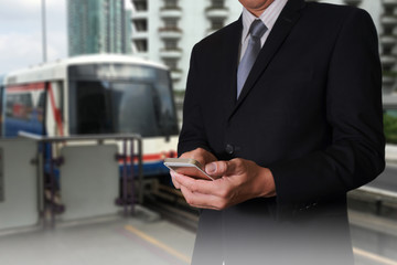 Business man hand hold smart phone, mobile on blurred abstract  Electric train background as communication and transportation concept.