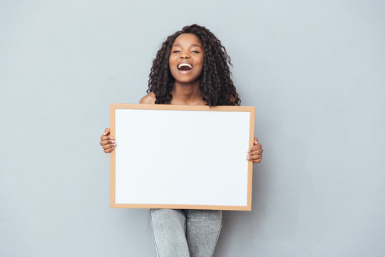 Cheerful afro american woman showing blank board