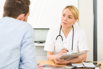 Young attractive woman doctor taking notes while patient speak