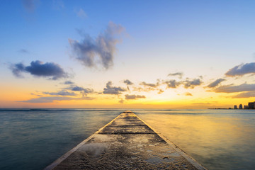 Long exposure at sunset of cement pier jutting out into Pacific Ocean near Waikiki Beach in Honolulu, Hawaii, USA