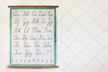 School poster with the alphabet in front of retro wallpaper