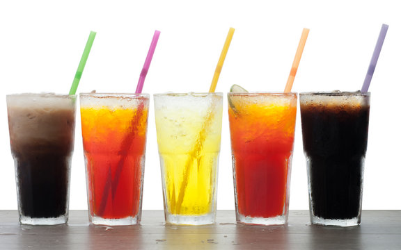 Four glasses of cold, fresh, homemade sodas with ice and drinkin