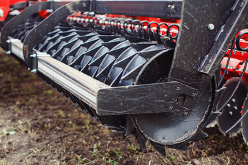 Plow modern tech red tractor close up on an agricultural field Mechanism