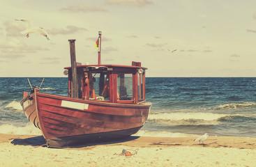 Ein alter Fischkutter am Strand im retro look