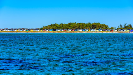 Lots of colorful bathing huts along the shore with a small forest behind. Calm and blue water in front. Falsterbo, Sweden.