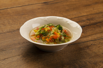 Bowl of minestrone Italian vegetable soup in white porcelain bowl on a wooden table