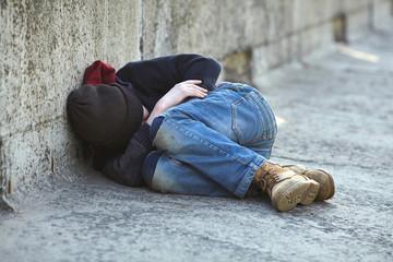 young homeless boy sleeping on the bridge