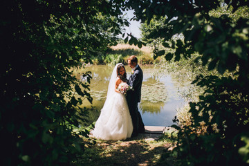 wedding couple in a private moment of joy on the forest lake