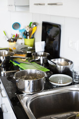Dirty pans, plates, cutting boards and other kitchen utensils on the kitchen countertop. Selective focus.