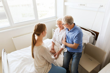 happy family visiting senior woman at hospital