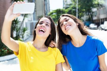 Zwei Freundinnen in bunten Shirts machen Selfies