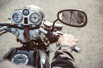Senior man hand steering motorcycle on road