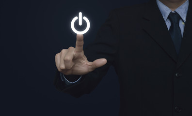 Businessman pressing power button on blue background
