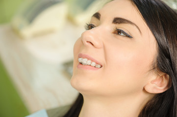 Portrait of young beautiful smiling woman with ceramic braces on teeth at the dental office