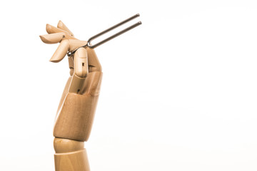 Hand sets the tone with a tuning fork. On white background.