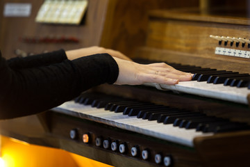Hands of a woman playing the organ