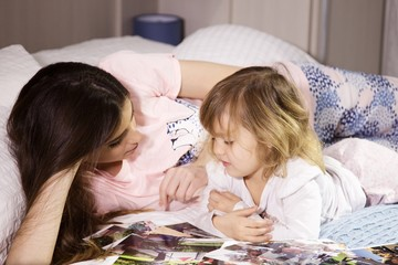 Young woman in bed with daughter looking pictures happy