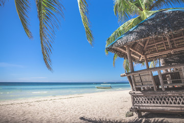 Traditional philippine bamboo hut against background with turquoise sea or ocean and palm leaves in the foreground. Panglao Island, Philippines.