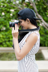Young woman photographer taking photo over green tourist attraction