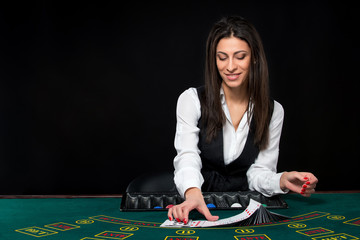 The beautiful girl, dealer, behind a table for poker